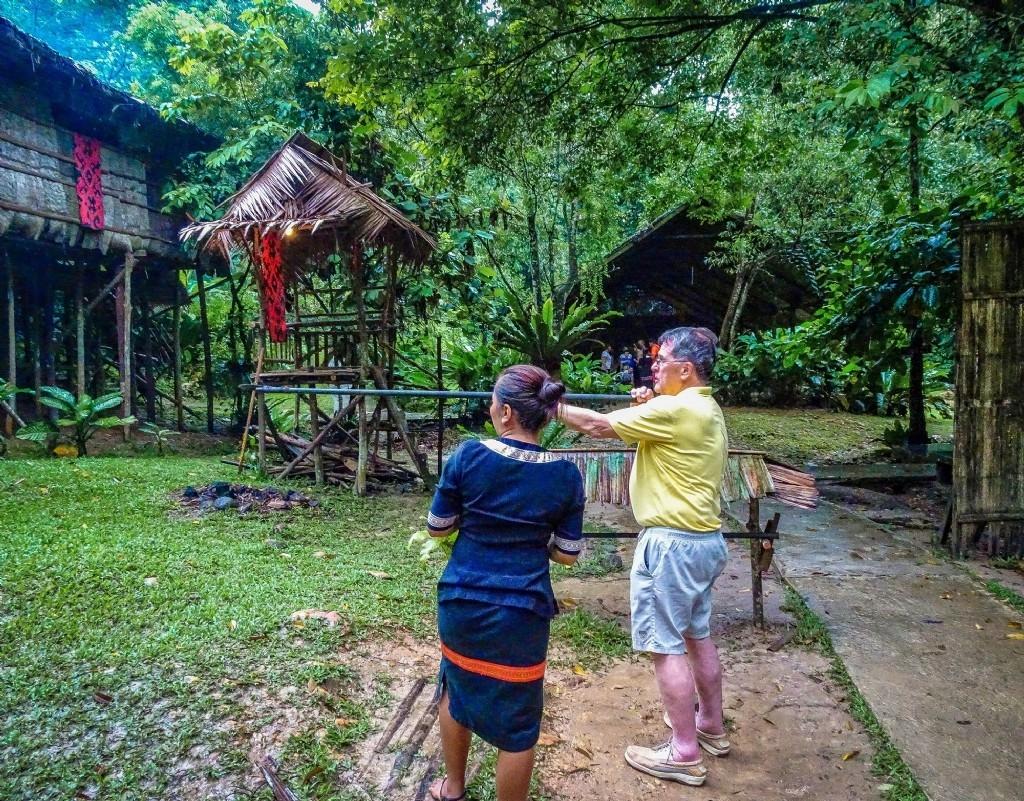 Trying a blowpipe - Mari Mari Tribal Village